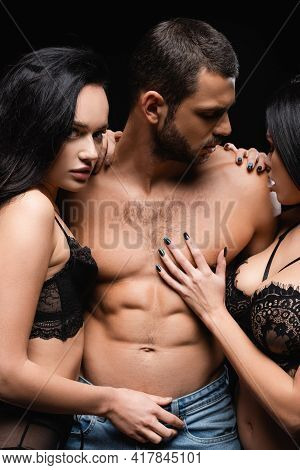 Passionate Women In Lingerie Embracing Man With Muscular Torso Isolated On Black.