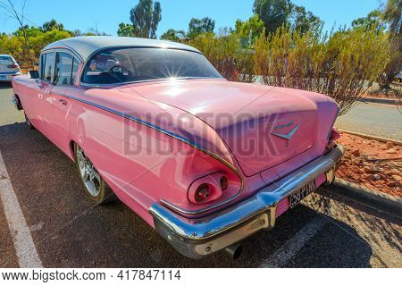 Yulara, Northern Territory, Australia - Aug 24, 2019: Rear View Of Luxurious Vintage Pink Chevrolet