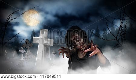 Scary Zombie At Misty Cemetery With Old Creepy Headstones Under Full Moon. Halloween Monster