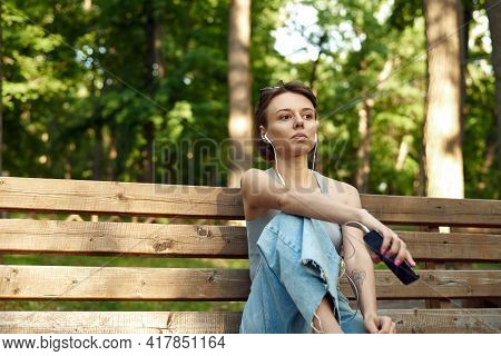 Beautiful Young Brunette Hipster Woman Listening Music In The Park On The Bench. Pretty Woman In The