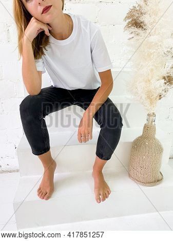 Beautiful Young Woman In Blank White T-shirt And Black Jeans Sitting On The Stairs