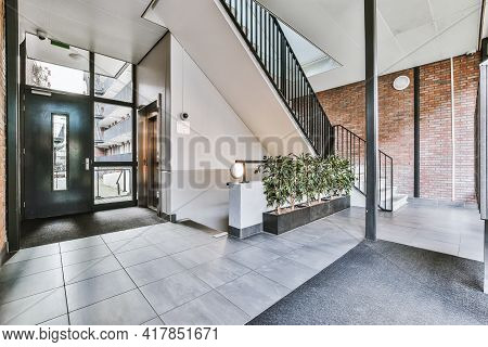 Staircase And Elevator Located Near Door And Brick Wall In Hall Of Contemporary Apartment Building