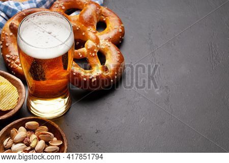 Lager beer mug, nuts, potato chips and fresh baked homemade pretzel with sea salt on stone table. Classic beer snack. With copy space