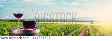 Red wine in decanter and glass, grapes on wine barrel in front of landscape of vineyard. Sunny summer day. French countryside valley