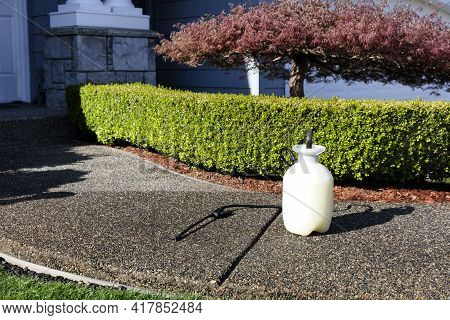 One Gallon Sprayer In Front Of Home Shrubs For Fertilizing, Insecticide And Herbicide