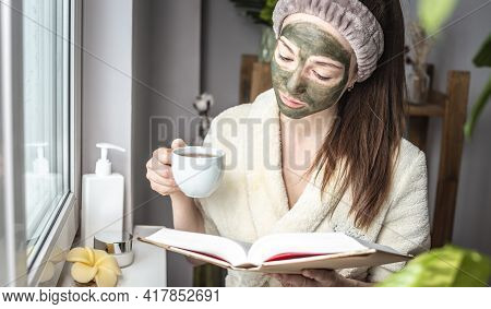 Pretty Young Woman In A Bathrobe And With A Green Cosmetic Mask On Her Face Is Reading A Book And Dr