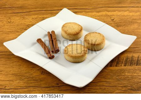 Three Spanish Cinnamon Mantecado Cookies With Cinnamon Sticks On White Snack Plate On Table