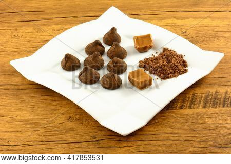 Cocoa Dusted Salted Caramel Truffles With Cocoa Powder And Caramel Squares On White Plate