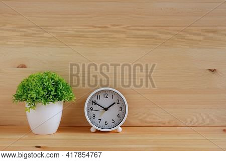 Table Clocks And Flower Vases On Wooden Desk. With Copy Space For Text.
