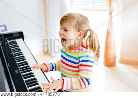 Beautiful Little Toddler Girl Playing Piano In Living Room. Cute Preschool Child Having Fun With Lea