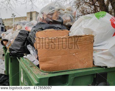 Dnepr, Ukraine- December 28, 2020: Big Metal Dumpster Garbage Can Full Of Litter Polluting City Stre