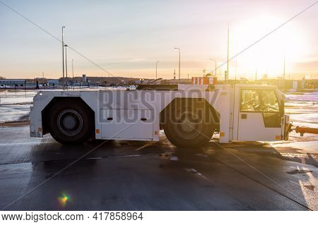 Aircraft Tow Tractor At The Airport Apron In The Light Of Evening Sun