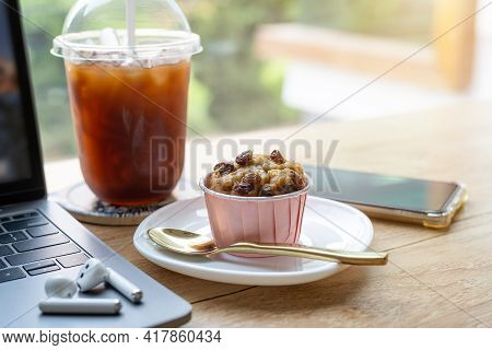 Close-up Of Homemade Banana Cup Cake And Ice Coffee In Cup Mug With Wireless Earphones On Laptop Com