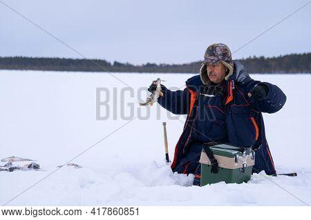 Ice Fishing. Fisherman Fishing On Frozen Lake. Winter Frosty Morning Fishing On River.
