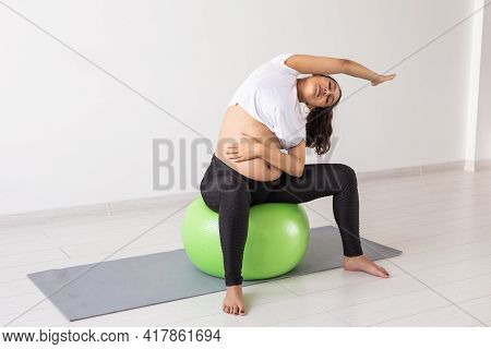 Young Flexible Pregnant Woman Doing Gymnastics With Fitness Ball. The Concept Of Preparing The Body
