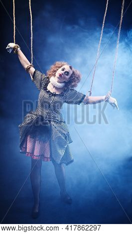 The actress plays a doll on strings at a performance in a puppet theater. Full length portrait in retro style.