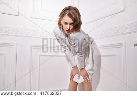Fashion shot. Glamorous young woman with evening makeup poses in elegant white dress and gemstone earrings. Beauty and jewelry.