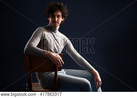 Portrait of a handsome young man with curly dark hair sitting on the chair on a black background. Men's beauty.