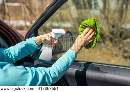 Car Windows Cleaning. Female Hands Cleaning Car Window With Green Microfiber Cloth And Spray Bottle