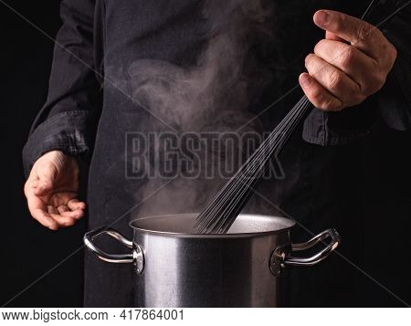 Pasta Cooking Process. Close-up Hands Of Cook, A Saucepan And Italian Black Spaghetti On The Backgro
