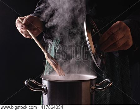 Close-up Open Saucepan Lid, Hands Of Cook On The Dark Background Of A Green Apron With Polka Dot. Ho