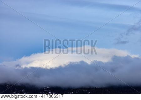 Puffy Clouds Over The Canadian Mountain Landscape. Colorful Winter Sunset Cloudscape Background. Tak