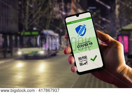 Smartphone Displaying A Valid Digital Green Passport For Covid-19 In Male's Hand, Downtown And City