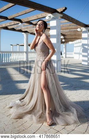 A Slender Brunette Girl In A Long Beautiful Evening Dress Spends Time Alone Outdoors On A Sunny Summ