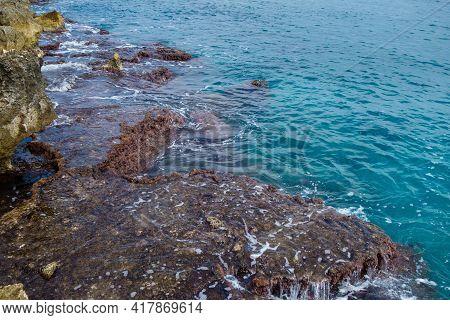 Coastline Rocks Washing By Sea Waves. Classic View For Mediterranean Shoreline Untouched By Human Ha