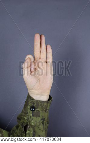 Hand In Camouflage Shows Gesture With His Fingers On Gray Background. Middle, Ring Finger And Little
