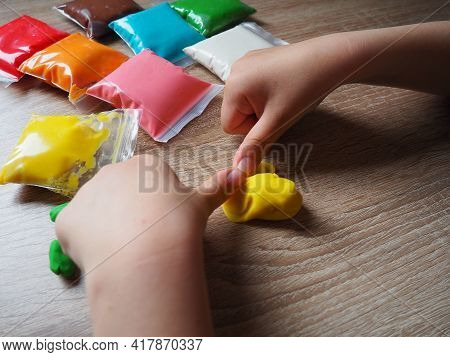 Children's Hands Crumple Soft Plasticine. Packages With Plasticine Are On The Table. Creativity For