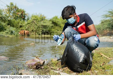 Frontline Worker Or Volunteer Collecting Trapped Discarded Face Mask Near Lake Or River Water And Pl