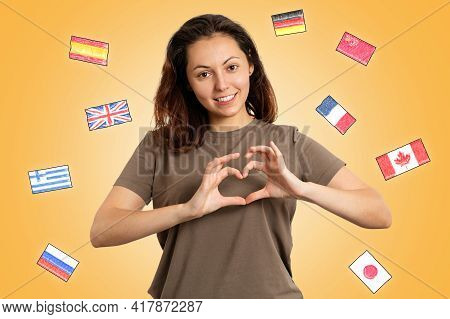 Concept Of Learning Foreign Languages. A Young Smiling Woman Shows A Heart Gesture With Her Hands. Y