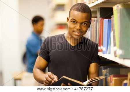 male african college student reading in library