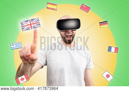 A Happy Man In Virtual Reality Glasses Clicks On The Flag Of The United Kingdom On The Virtual Inter