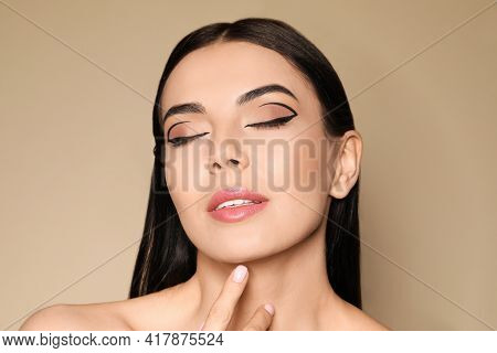 Beautiful Woman With Black Eyeliner On Beige Background