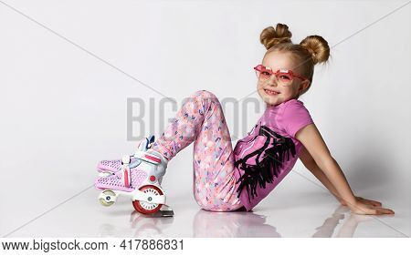 Cute Blonde Girl In A Pink Sweater With A Print And Legends Sits On The Floor In Roller Skates. Stud