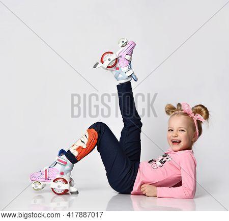 Full Body Portrait Of Positive Funky Little Girl In Roller Skates Sitting On Studio Floor Advertisin