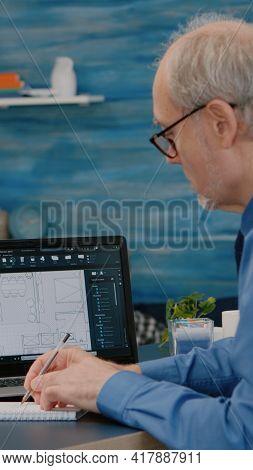 Senior Man Architect Analysing Digital Prototype With Plans From Laptop