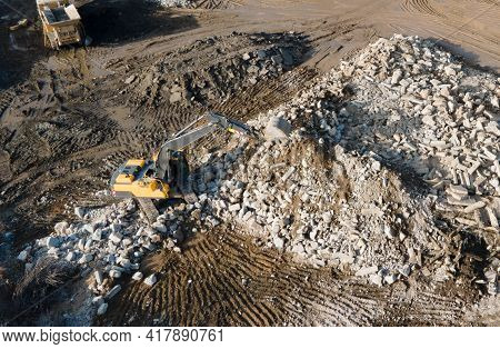 Recycling Concrete And Construction Waste From Demolition. Excavator At Landfill Of The Disposa. Reu