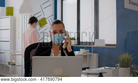 Entrepreneur With Protective Face Mask Discussing On Landline