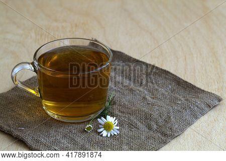 Hot Drinks. Mug Of Chamomile Tea On Sackcloth. Glass Cup Of Hot Herbal Chamomile Tea On A Wooden Tab