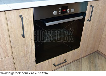 Modern Kitchen With Electric Oven, Electic Stove. Brown And Gray Wooden Countertops. Built-in Househ