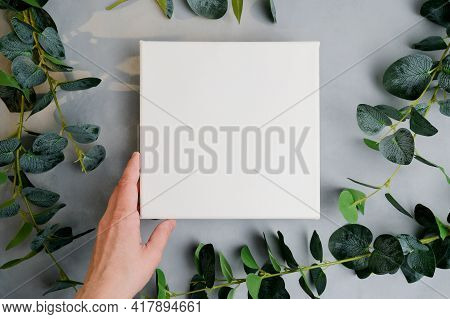 Female Hand With White Canvas Frame, Green Plant Branches On Background. Wrapped Blank Canvas For Mo
