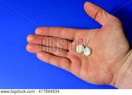Pills In Hand On Blue Background. Medicine Grade Pharmaceutical Tablets. Medical Pill For Maintainin