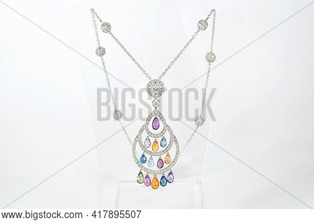 Golden Necklace With Diamonds On Transparent Jewelry Neck Stand In Boutique. White Gold With Diamond