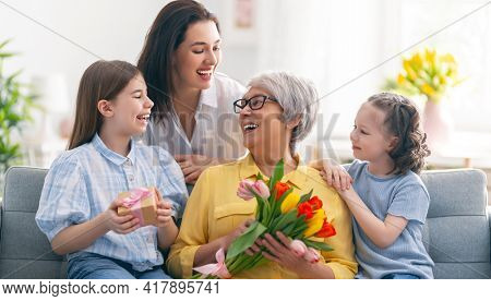 Happy mother's day! Child daughters and mother are congratulating granny giving her flowers tulips. Grandma, mum and girls smiling and hugging. Family holiday and togetherness.