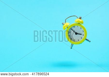 Yellow Retro Alarm Clock Levitates. Alarm Clock In The Old Style On A Blue Background. 15-55 Pm. The