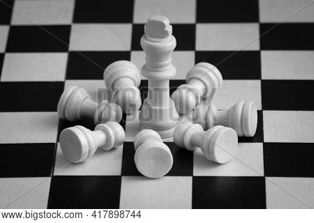 White Chess Pieces, King Surrounded By Lying Pawns, On Chessboard. Concept Of Leadership.