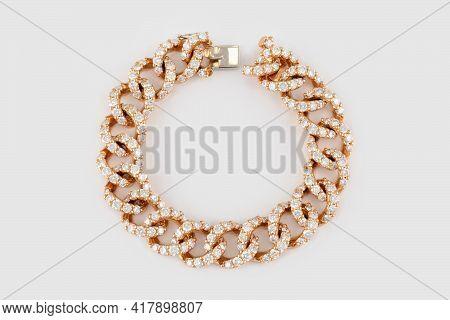 Golden Bracelet With Diamonds On Gray Background. Luxury Yellow Gold Diamond Jewelry Bracelet.